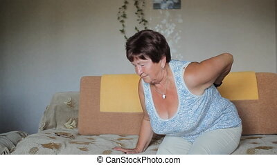 Adult woman has a backache. A woman tries to get up from the couch, but she has a sharp pain in the back