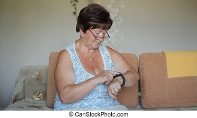 Old woman touch smart watch at home