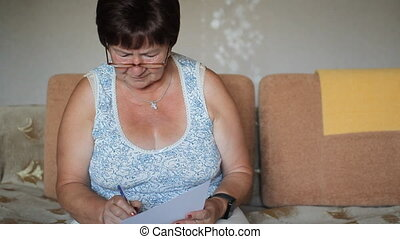 Senior woman signing a contract at home. She carefully reads...