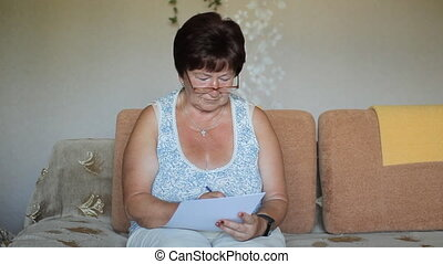 Senior woman signing a contract at home She carefully reads...