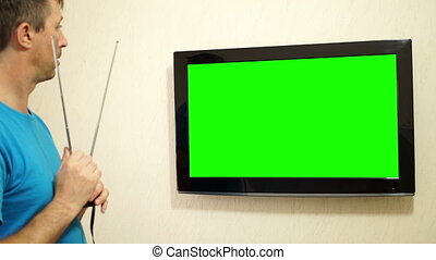 TV Adjusting Antenna Green Screen - Male holding and...