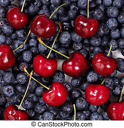 Fresh blueberries and cherries in filled frame format -...
