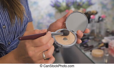 A makeup artist using a brush with the powder - A makeup...