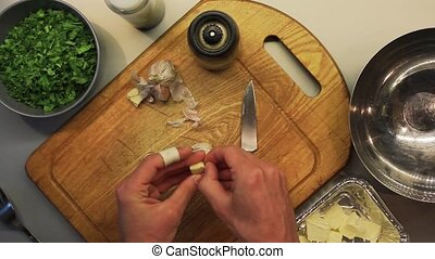 Male hands peeling and cutting garlic on a wooden cooking...
