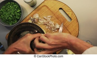 Male hands mixing chopped garlic, greens, pepper and butter...