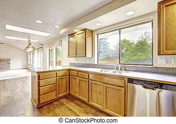 Kitchen with golden wood cabinets and hardwood floor.