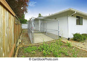 One story house exterior. Fenced Backyard view with cage....