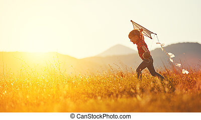 happy child girl with a kite running on meadow in summer in...