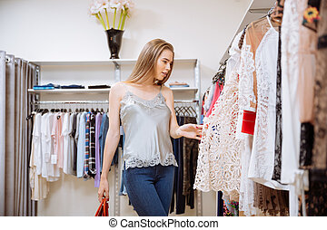 Stylish woman choosing clothes in shop