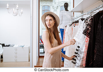 Pretty woman choosing clothes and doing shopping in clothing...