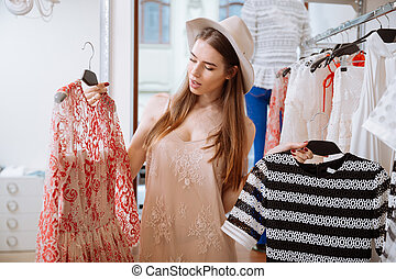 Pensive young woman choosing clothes in shop - Pensive young...