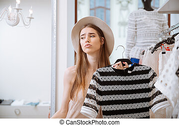 Sad pretty young woman in hat doing shopping in clothing...