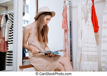 Relaxed woman sitting and reading magazine in clothing store...