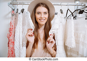 Happy pretty young woman choosing clothes in clothing store...