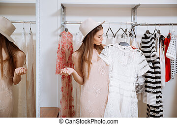 Pensive woman standing and choosing dress in clothing store...