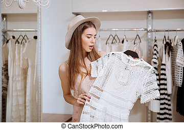 Amazed young woman holding and choosing dress in fashion...