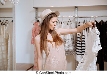 Thoughtful woman holding and looking at dress in clothing...