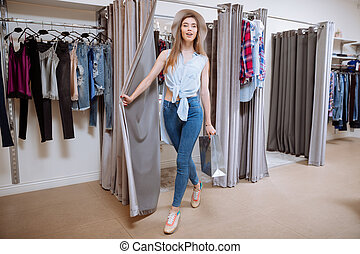 Smiling woman with shopping bag going out of fitting room -...
