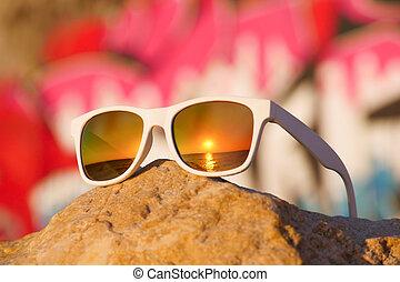 sunglasses lying on rock on background of graffiti
