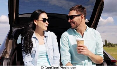 happy couple with coffee at hatchback car trunk 41