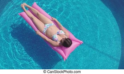 Woman relaxing in a small home pool - Woman relaxing in a...