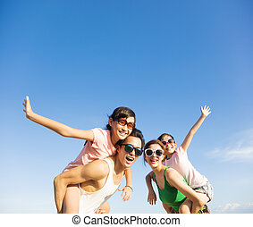 happy family having fun outdoors against blue sky background