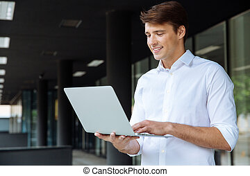 Cheerful businessman standing and using laptop