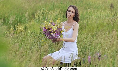 One young woman sitting on green field with flower bunch