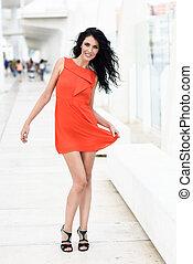 Brunette woman wearing orange short dress in the street -...