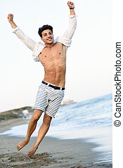 Portrait of an attractive young man on a tropical beach -...