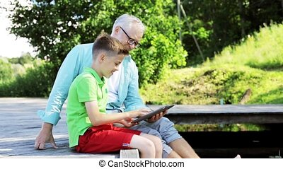 grandfather and boy with tablet pc on river berth 32 -...