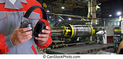 Worker with protective headphone at man hands at industrial...