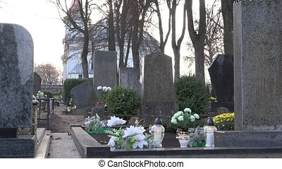 Candles burn between grave stones in cemetery and church in...