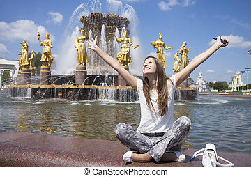 Young beautiful woman has a rest sitting near the fountain -...