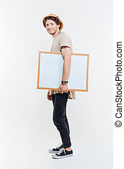 Full length of young man walking and holding blank whiteboard