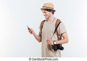 Portrait of a smiling man with backpack using smart phone -...