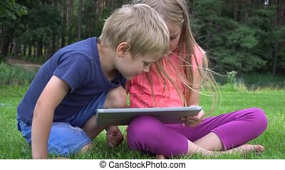 two kids playing with tablet outdoors