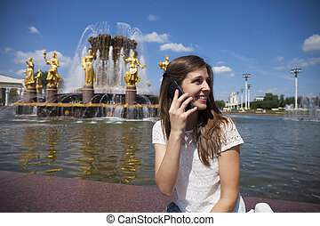 Young brunette woman calling by phone - Beautiful young...