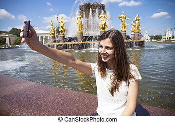 Smiling woman take a picture of herself with a smartphone...