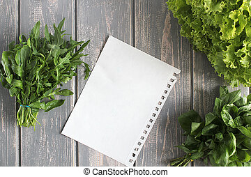 Sheet and composition of vegetables on grey wooden desk...