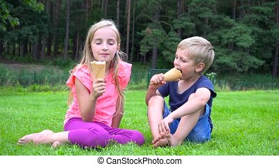 kids eating icecream outdoors - two kids eating icecream...