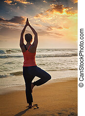 Young sporty fit woman doing yoga tree asana on beach - Yoga...