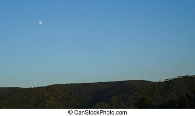 Footage the moon moves across the sky over the mountains 4K...