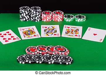 green casino table with royal flush, red and black chips