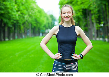 Cheerful young woman before a running session - Portrait of...