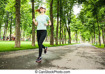 Full length portrait of a female runner running in the park....