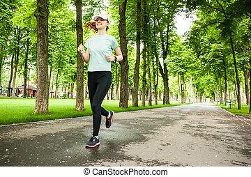 Full length portrait of a female runner running in the park....