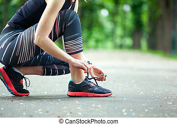 Closeup young woman tying her laces before a run - Close up...