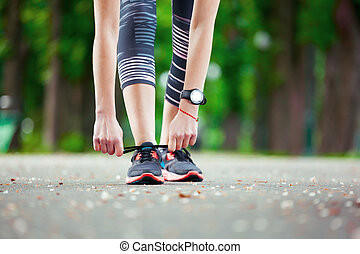 Close up of young woman tying her laces before a run - Shot...