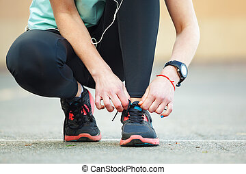Closeup young woman tying her laces before a run. - Close up...